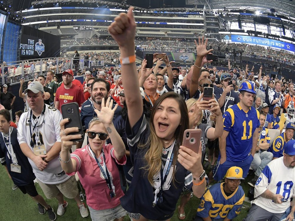 Dallas Cowboys fans celebrate as former Cowboys scout Gil Brandt announces Dorance Armstrong Jr., as the team's fourth-round pick during the final day of the 2018 NFL Draft at AT&T Stadium in Arlington, Texas, on Saturday, April 28, 2018. (Max Faulkner/Fort Worth Star-Telegram/TNS)
