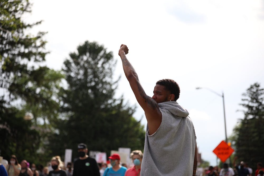<p>Ishmael El-Amin, junior Ball State Basketball guard, hold his fist in the air while the peaceful protest marches by, June 4, 2020, on University Avenue. The protesters marched from Shafer Tower to Muncie City Hall. <strong>Jacob Musselman, DN</strong></p>