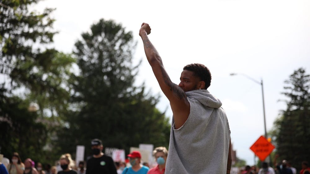 Ishmael El-Amin, junior Ball State Basketball guard, hold his fist in the air while the peaceful protest marches by, June 4, 2020, on University Avenue. The protesters marched from Shafer Tower to Muncie City Hall. Jacob Musselman, DN