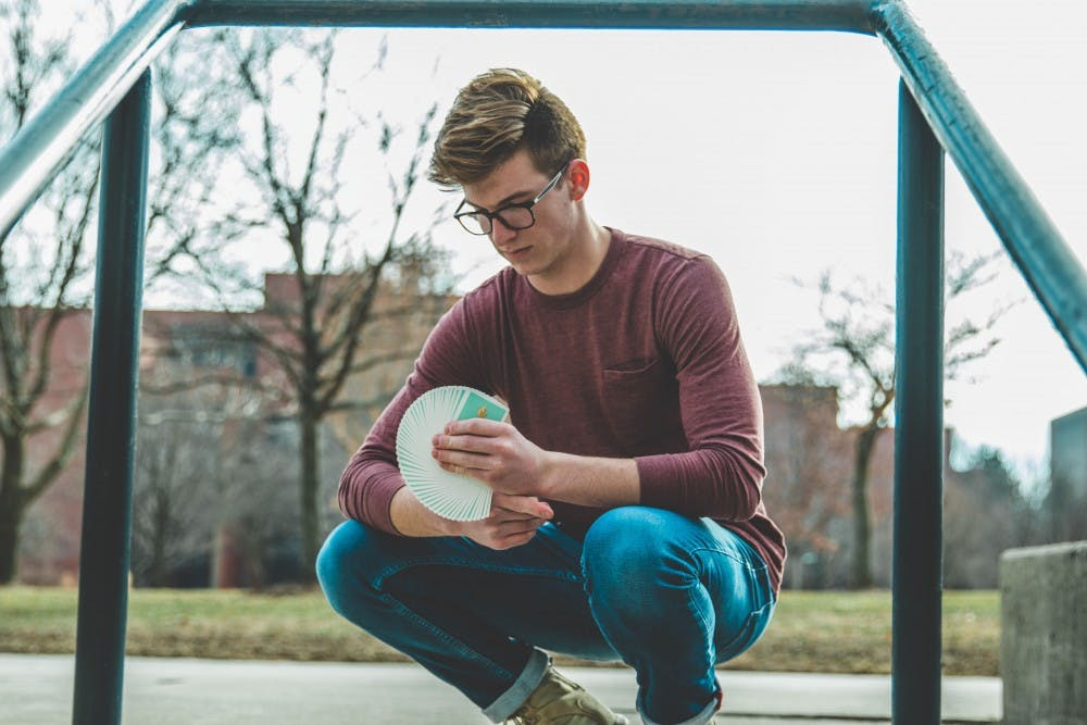 Junior telecommunications major Nate Lex does cardistry with the Peelers deck of Organic Playing Cards in 2018. Lex began cardistry in 2013 as a way to channel his energy because he said he has ADHD and has always been fidgety. Cameron Toner, Photo Provided.