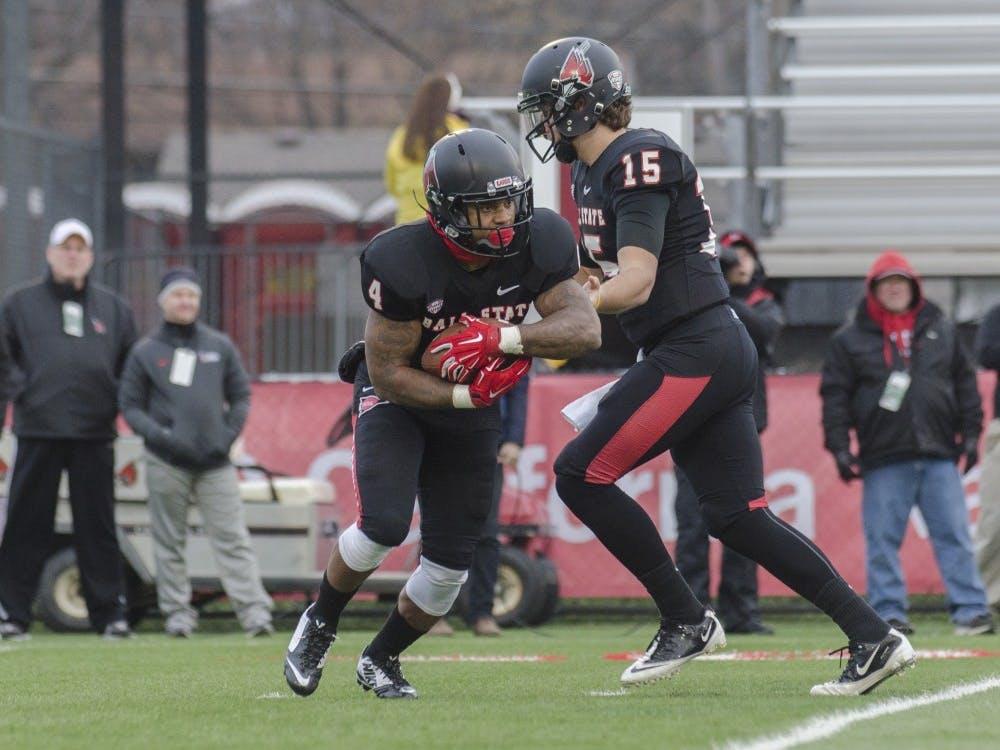 Redshirt sophomore quarterback Ozzie Mann hands the ball to redshirt junior running back Horactio Banks during the game against Eastern Michigan on Nov. 22 at Scheumann Stadium. DN PHOTO BREANNA DAUGHERTY