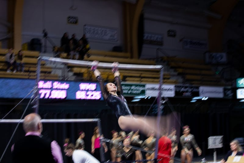 A Western Michigan gymnast performs her uneven parallel bar routine against Ball State Feb. 9, 2020, at Read Fieldhouse in Kalamazoo, Michigan. The Broncos beat the Cardinals 195.750-193.675. Jacob Musselman, DN