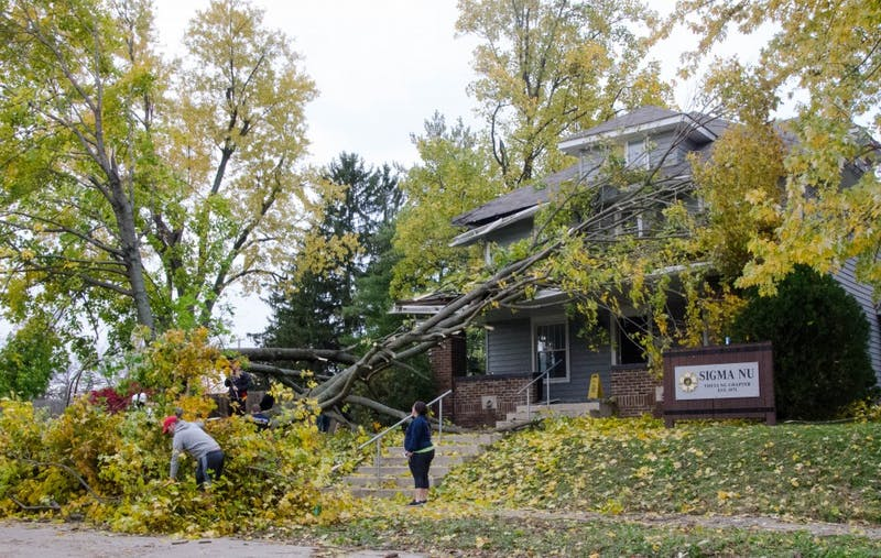 Students help move branches out of the Sigma Nu Theta Nu Chapter on Beachwood Avenue. Thousands of residents lost power after a brief EF-1 tornado touched down in Muncie Sunday. Power is still being restored and damage is still being assessed. Mary Freda, DN