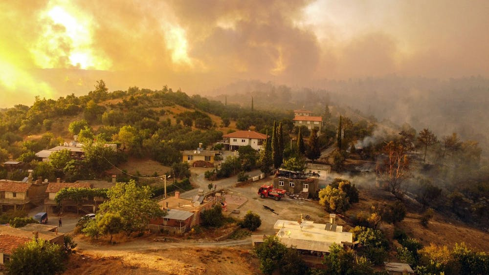 This aerial photograph shows houses surrounded by a wildfire which engulfed a Mediterranean resort region on Turkey's southern coast near the town of Manavgat, on July 30, 2021. (AFP/Getty Images/TNS)