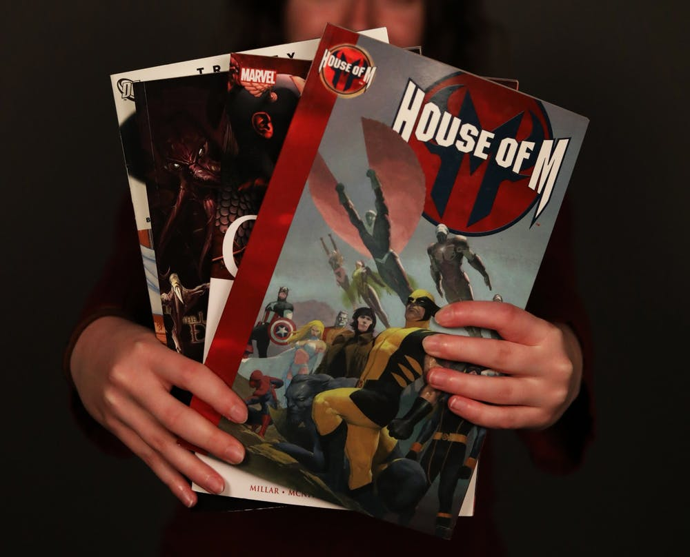 Sophomore journalism major, Emily Hunter holds several of her favorite comic books, March 23, 2021, in the photojournalism studio. Rylan Capper DN