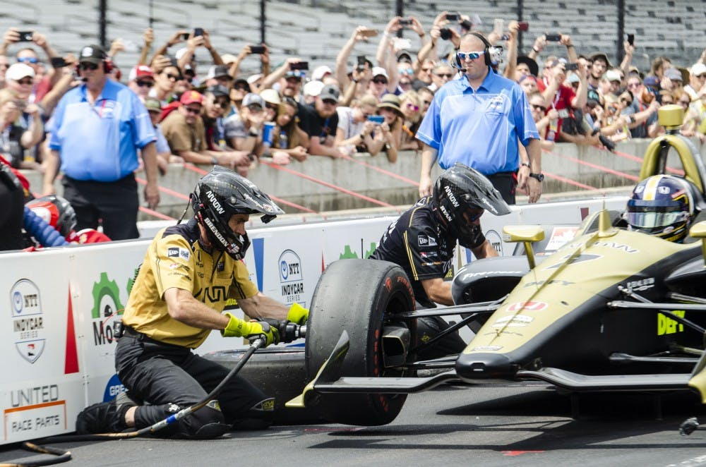 Brendon Cleave, damper engineer for Arrow Schmidt Peterson Motorsports, quickly changes a tire on Marcus Ericsson's car during the pit stop challenge May 24. Arrow SPM won $50,000 after beating Scott Dixon's time of 13.132 seconds. Stephanie Amador, DN