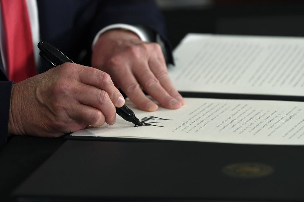 <p>President Donald Trump signs an executive order during a news conference at the Trump National Golf Club in Bedminster, N.J., Saturday, Aug. 8, 2020. (AP Photo/Susan Walsh)</p>