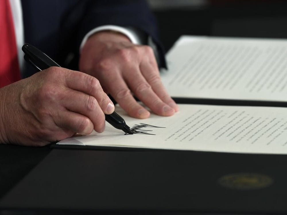 President Donald Trump signs an executive order during a news conference at the Trump National Golf Club in Bedminster, N.J., Saturday, Aug. 8, 2020. (AP Photo/Susan Walsh)