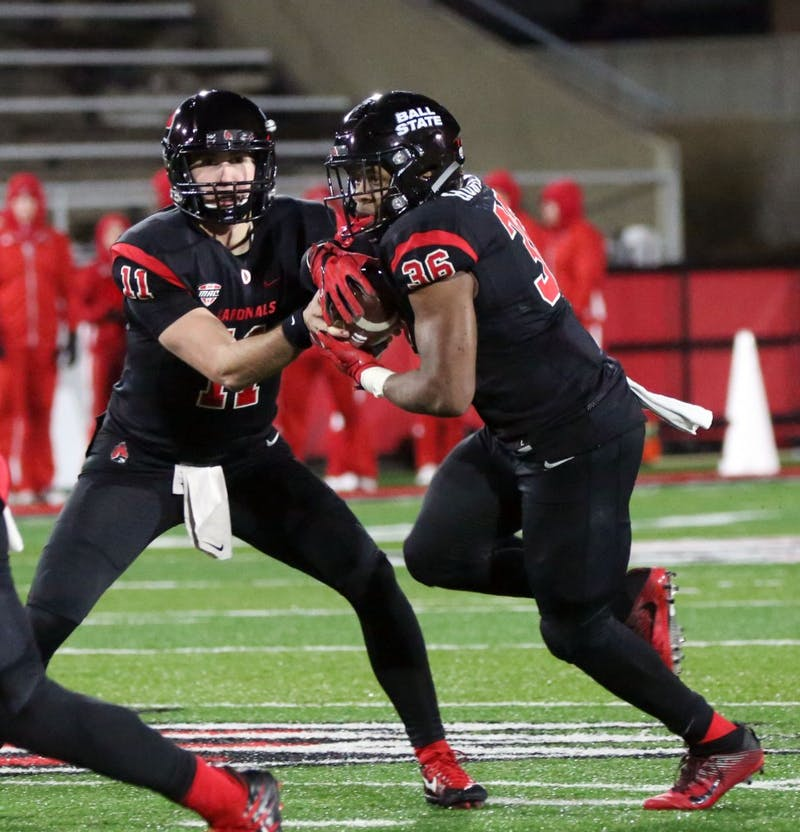 Redshirt freshman quarterback Drew Plitt hands the ball off to freshman running back Caleb Huntley the Cardinals' game against Miami Ohio on Nov. 21 at Scheumann Stadium. Ball State lost 7 to 28 on senior night. Paige Grider, DN