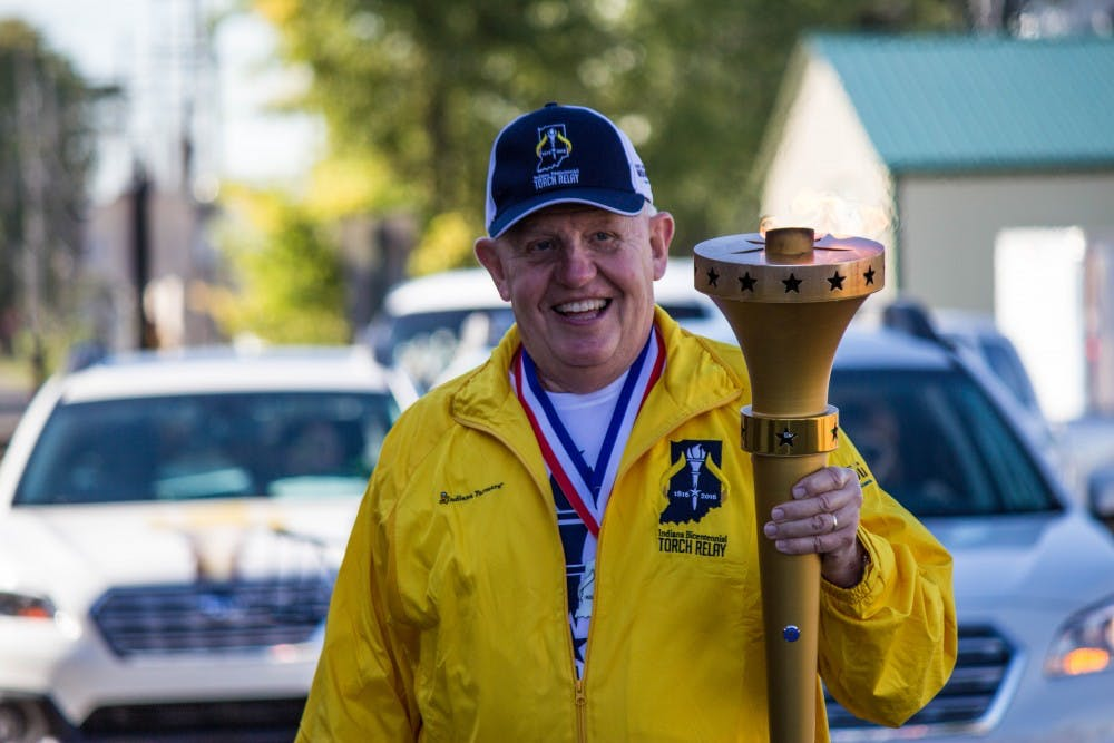 Alan Wilson, the 11th torchbearer, carries the torch through part of Delaware County on Sept. 27 for the Indiana Bicentennial Torch Relay. The relay started on Sept. 9 and will travel to all 92 counties in Indiana, and end on Oct. 15 in Indianapolis. Grace Ramey // DN