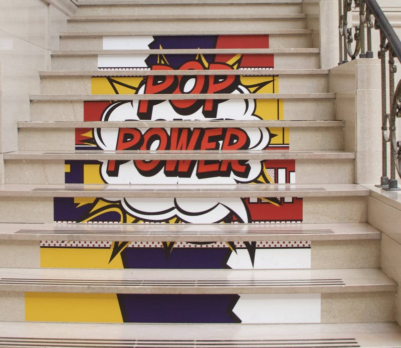 """POP Power"" stickers sit on the stairs of the David Owsley Museum of Art (DOMA) May 11, 2021. DOMA Director Robert La France said staff wanted to experiment with stickers leading people to the second floor of the special exhibition instead of signs with arrows. Grace McCormick, DN"