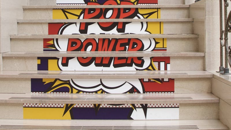 """""""POP Power"""" stickers sit on the stairs of the David Owsley Museum of Art (DOMA) May 11, 2021. DOMA Director Robert La France said staff wanted to experiment with stickers leading people to the second floor of the special exhibition instead of signs with arrows. Grace McCormick, DN"""