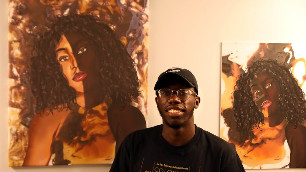 """Jaylyn Graham poses for a photo next to his artwork """"The Colorism Series,"""" Sept. 13 in the Multicultural Center. The new center near Bracken Library features student artwork and will soon accept applications for new displays. Rylan Capper, DN"""