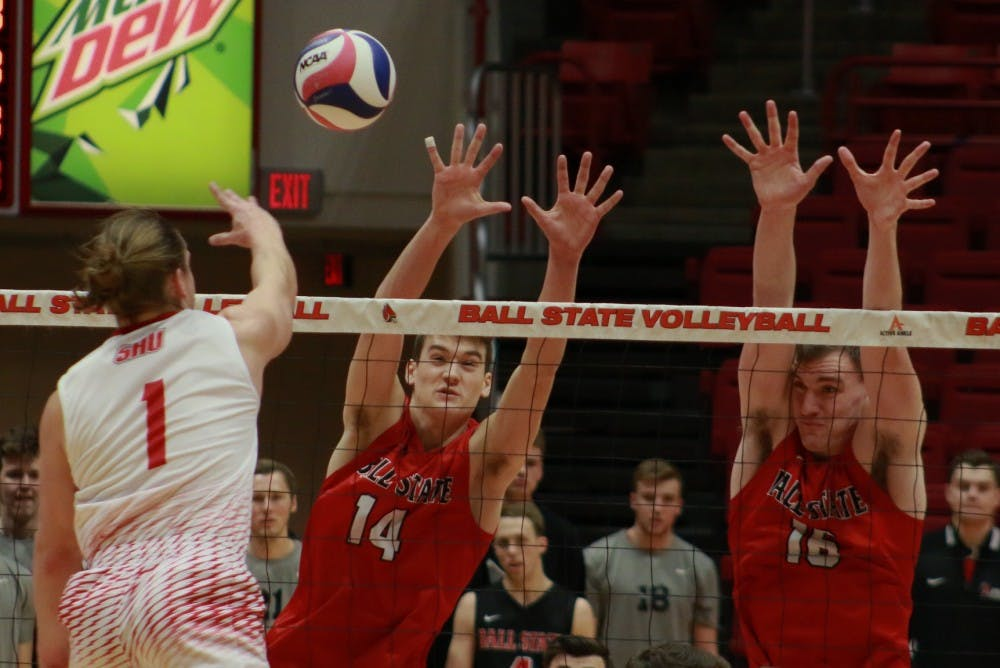 <p>Ball State sophomore Matt Szews and senior Matt Walsh just to block a spiked ball from Sacred Heart during the game against on Jan. 19. The Cardinals won 3-2. <strong>Carlee Ellison, DN</strong></p>