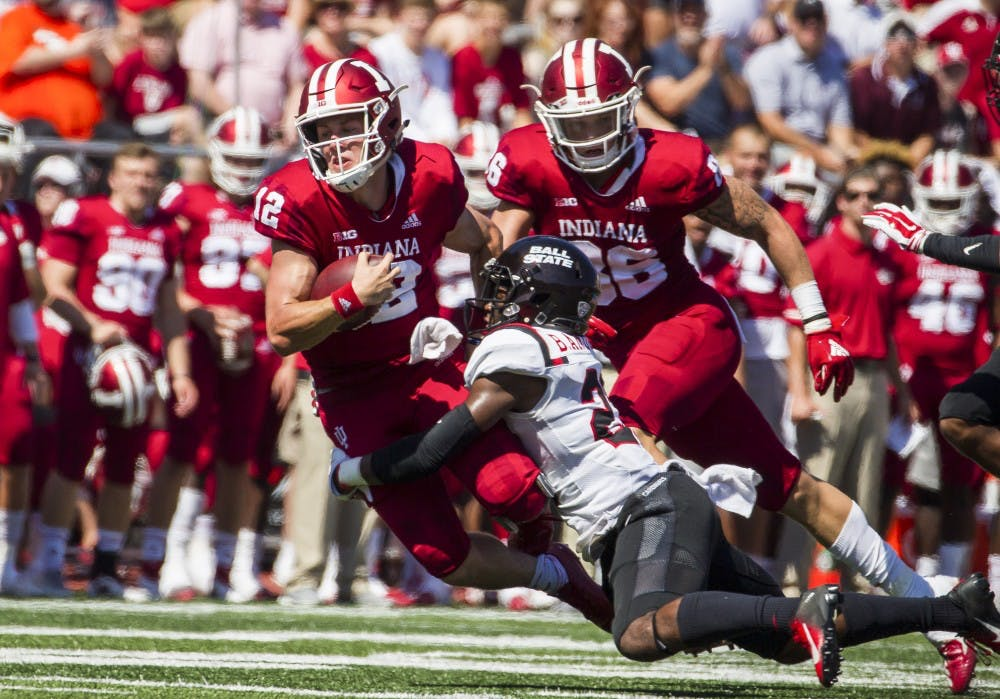 <p>Junior quarter back Peyton Ramsey rushed for a first down and tackled sophomore safety Brett Anderson II Saturday, September 15, at Memorial Stadium, in Bloomington, IN. Ramsey passed 173 yards for IU, helping defeat Ball State, 10-38. <strong>Grace Hollars, DN</strong></p>