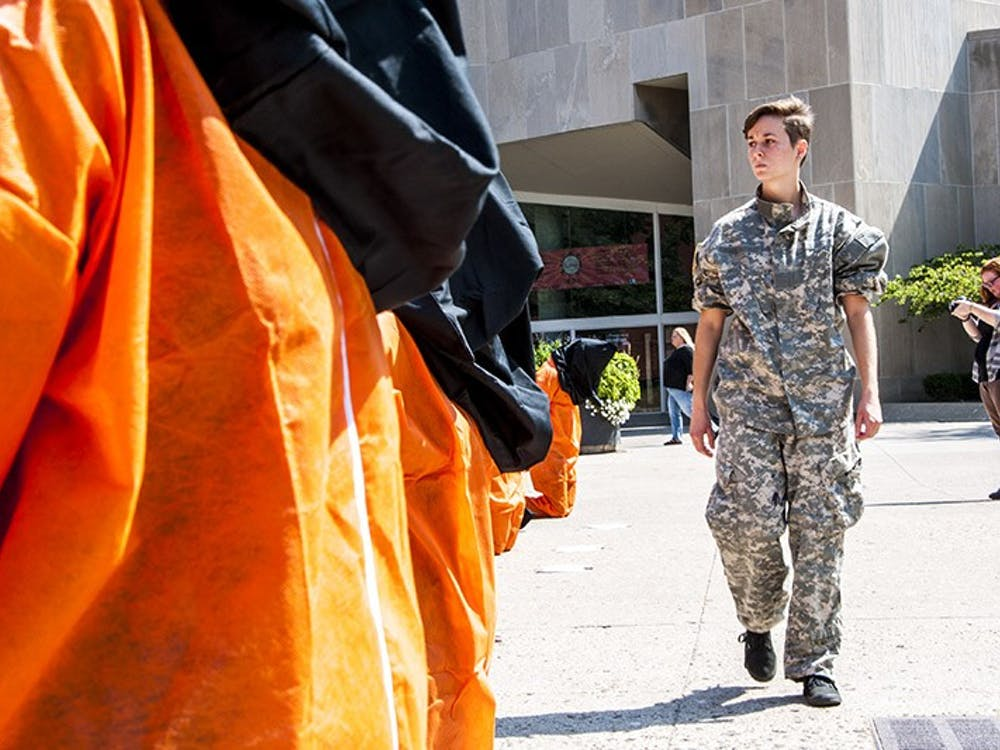 Senior telecommunications major Bianca Russelburg, dressed in military attire, paces infront of mock Guantanamo Bay detainees in front of Bracken Library on Aug. 28. Amnesty International organized the protest to bring attention to practices at the American detention center. DN PHOTO JONATHAN MIKSANEK