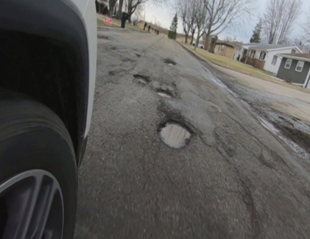 Potholes line W. Purdue Avenue between N. Lancaster Drive and N. Oakwood Avenue on Feb. 18, 2020.