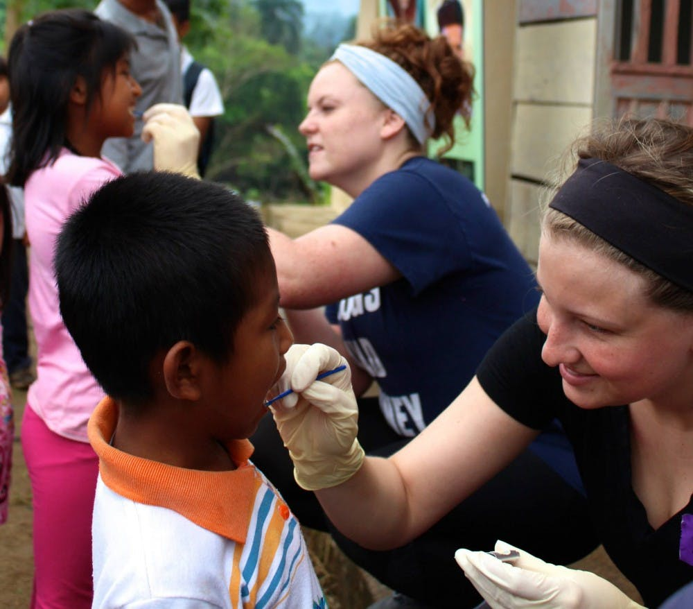 <p>A member of Timmy Global Health cleans a child's teeth with fluoride in 2016 in Ecuador. Ball State's chapter of Timmy Global Health visited Ecuador to provide healthcare options to the community. Ella Penczek, Photo Provided.&nbsp;</p>