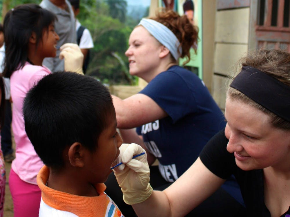 A member of Timmy Global Health cleans a child's teeth with fluoride in 2016 in Ecuador. Ball State's chapter of Timmy Global Health visited Ecuador to provide healthcare options to the community. Ella Penczek, Photo Provided.