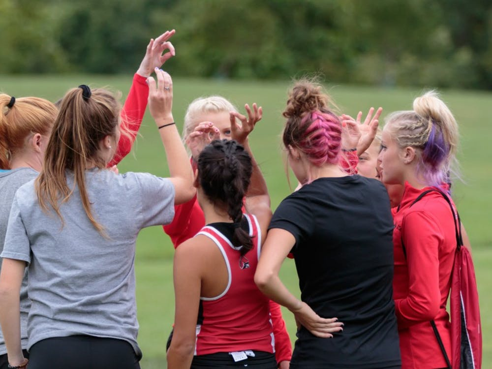 The Ball State Women's Cross Country team huddles up before the Butler Twilight meet at NorthView Church on Sept. 1, in Carmel, IN. The Cardinals placed third with a total score of 55. Kyle Crawford, DN