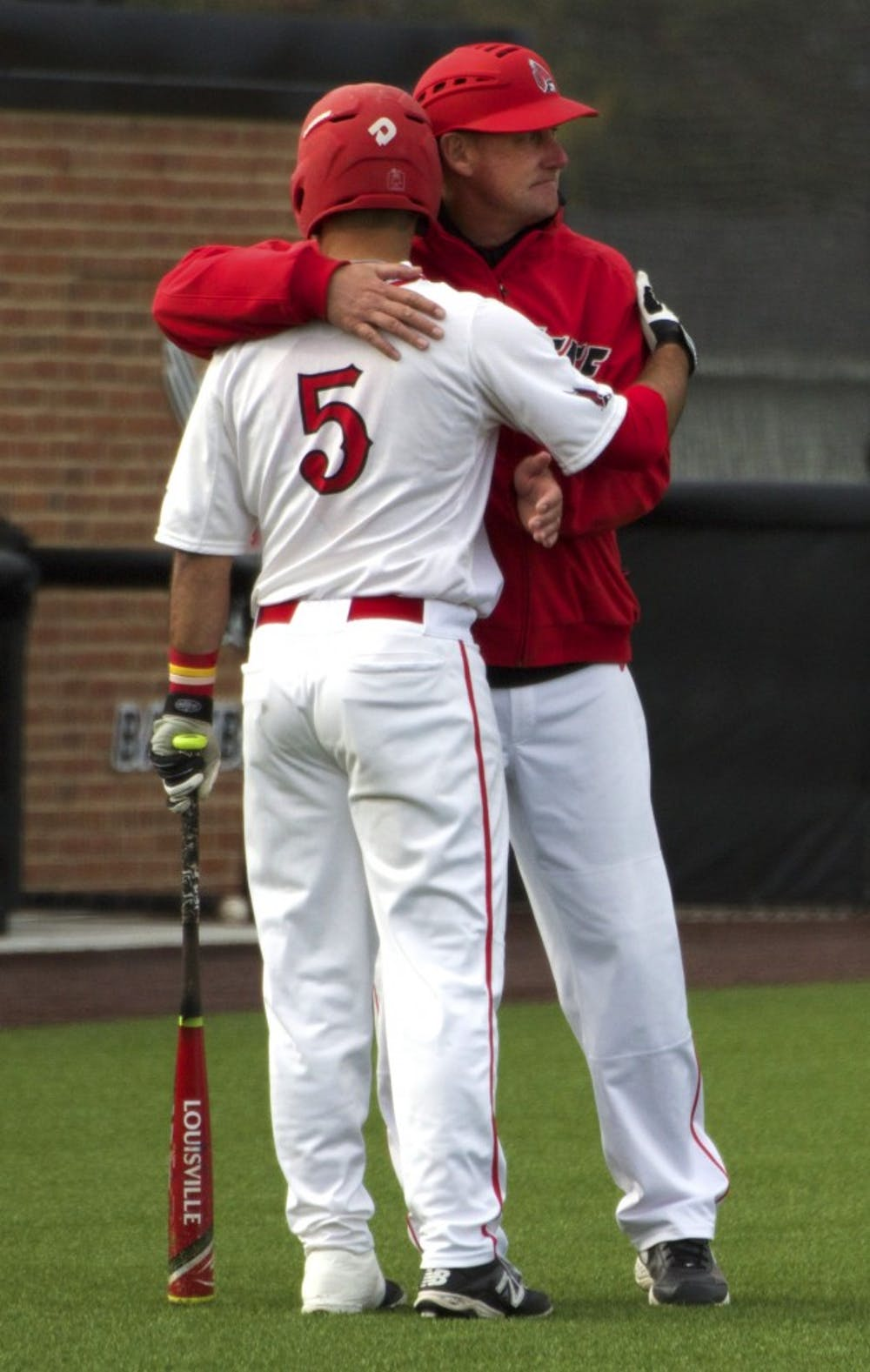 Ball State's head baseball coach Rich Maloney gives senior infielder Ryan Spaulding a hug while the players from Ohio take a time out in the game on April 1. DN PHOTO GRACE RAMEY