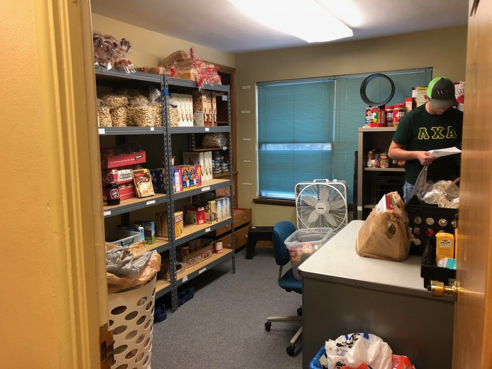 Trevor Millspaugh gathers food for a client in Cardinal Kitchen's nine-by-12 foot stockroom in the Multicultural Center. Cardinal Kitchen is currently crowdfunding to relocate to a different space. Sara Barker, DN