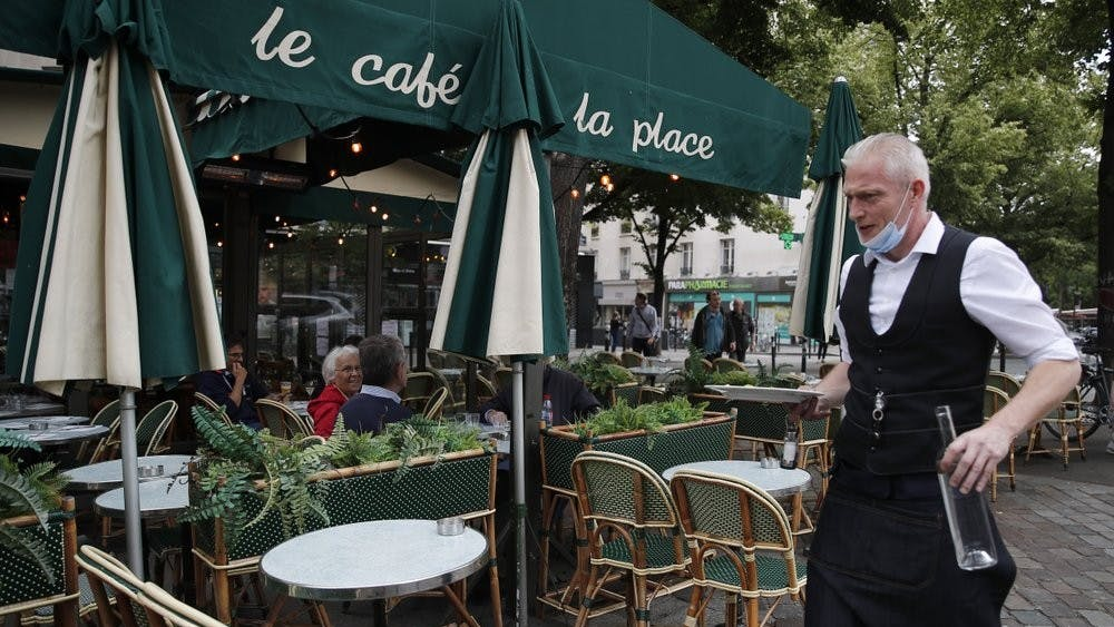 A waiter walks to serve customers at a restaurant, June 15, 2020, in Paris. Paris is rediscovering itself, as its cafes and restaurants reopen for the first time since the fast-spreading virus forced them to close their doors March 14. (AP Photo/Francois Mori)