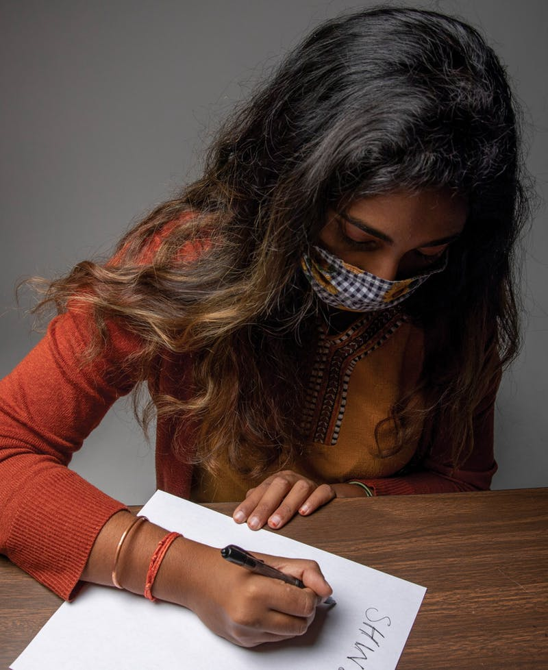 Shwetha Sundarrajan writes down misspellings of her name Nov. 3, 2020, in the photojournalism studio. Throughout Sundarrajan's life, her name has been misspelled and misspoken. Jacob Musselman, DN Illustration