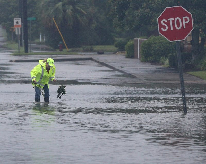 A city employee works to clear storm drains on flooded Isabella Street in the downtown area as Hurricane Irma moves through the city on Sept. 11 in Waycross, Ga. TNS Photo