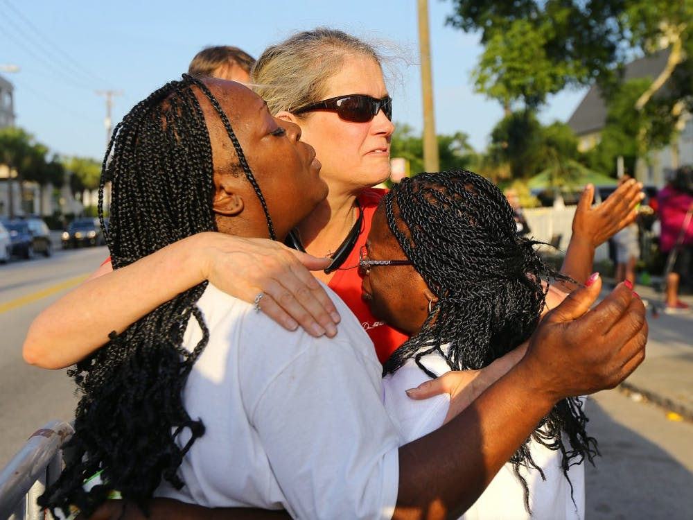 "Crissa Jackson, from left, Cynthia Coates and Cynthia Jackson embrace one another and pray as they wait in line for the doors to reopen to the ""Mother"" Emanuel A.M.E. Church on Sunday, June 21, 2015, in Charleston, S.C. (Curtis Compton/Atlanta Journal-Constitution/TNS)"