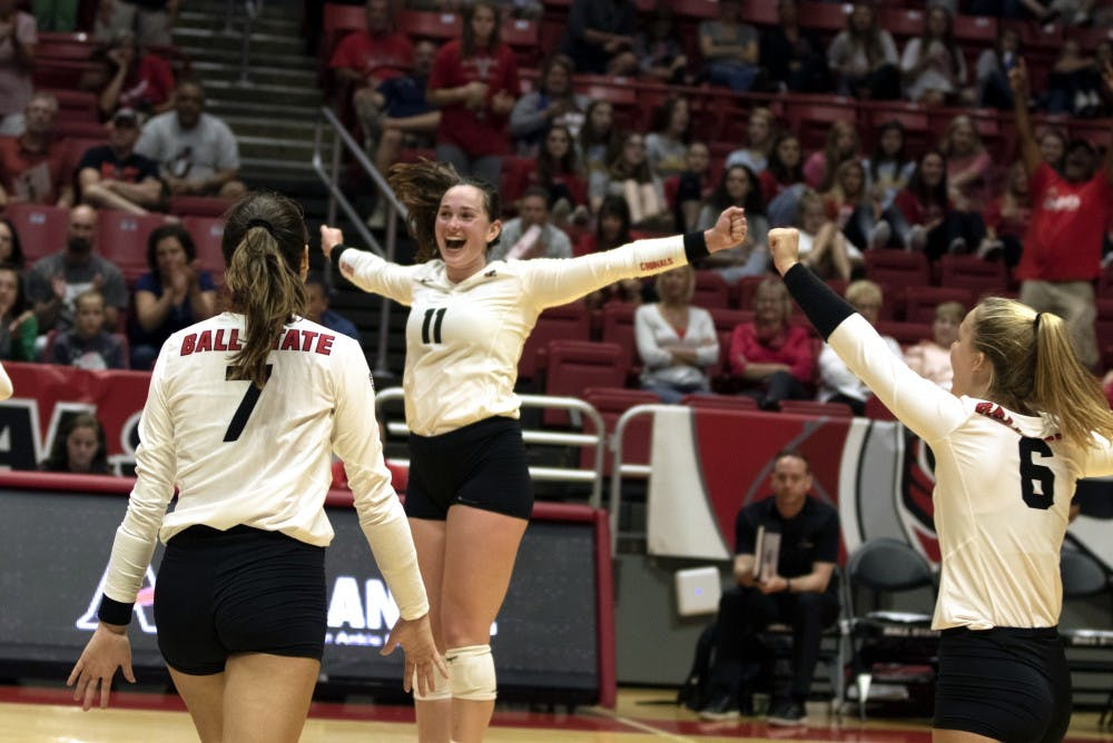 <p>Natalie Risi (7), Amber Seaman (11), and Maggie Huber (6) &nbsp;celebrate winning their second match against Austin Peay on September 20, 2019, at Worthen Arena. Ball State continued on to win 3-0. <strong>Jaden Whiteman, DN</strong></p>