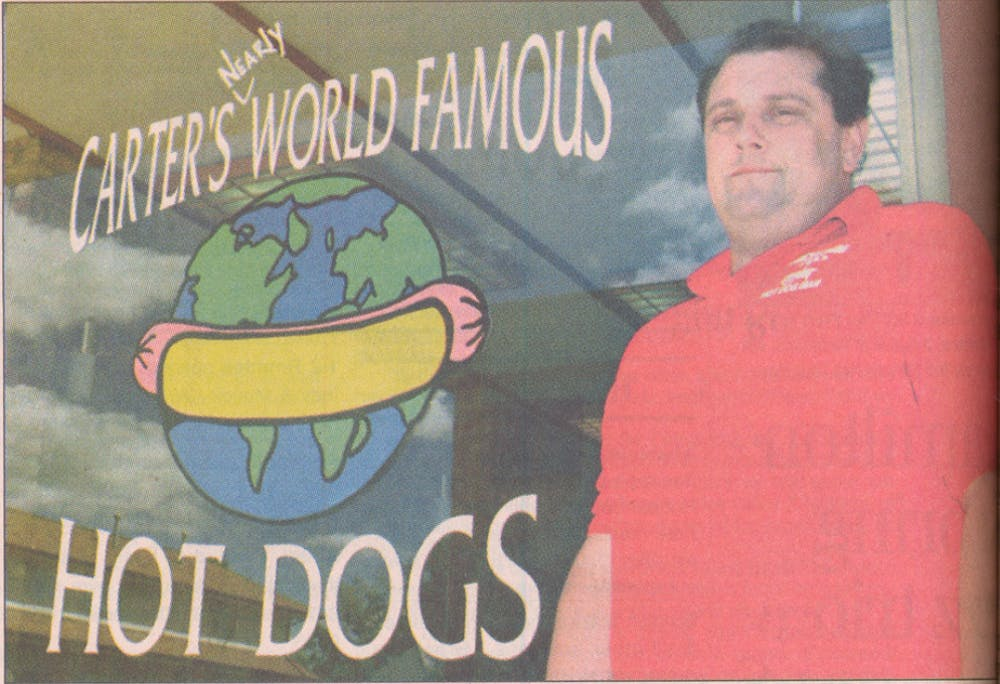 This image from 1998 shows Mark Carter, owner and operator of Carter's Nearly World Famous Hot Dogs, standing in front of his store in the Village. Carter's store used to be located where Jimmy John's sits today. Digital Media Repository, Photo Courtesy