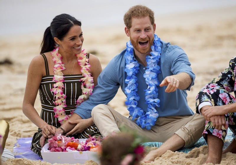 FILE - In this Friday, Oct. 19, 2018 file photo Britain's Prince Harry and Meghan, Duchess of Sussex meet with a local surfing community group, known as OneWave, raising awareness for mental health and wellbeing in a fun and engaging way at Bondi Beach in Sydney, Australia. Buckingham Palace said Monday May 6, 2019, that Prince Harry's wife Meghan has gone into labor with their first child.(Dominic Lipinski/Pool via AP, File)