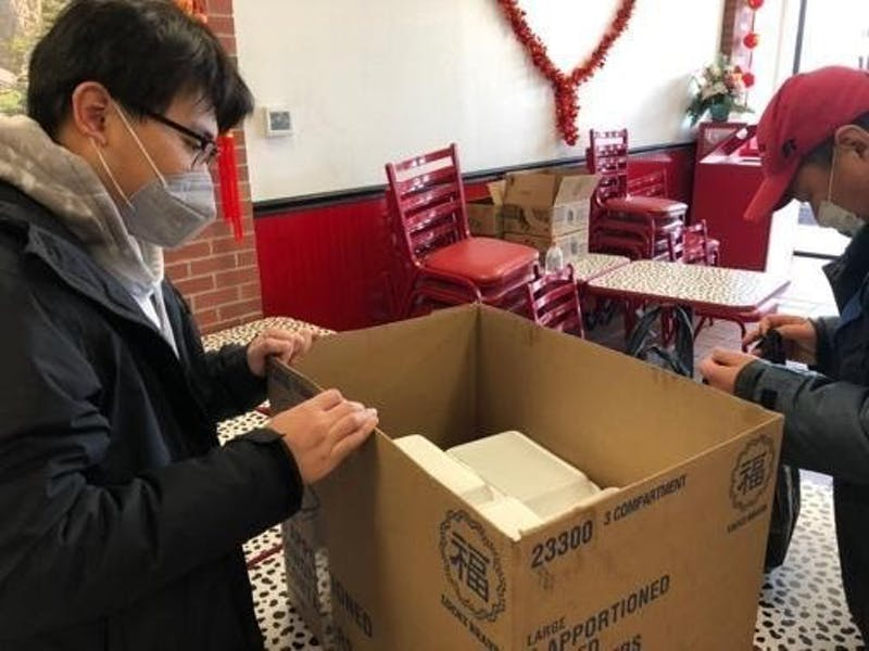 Senior journalism major Zi Wang packs boxes of to-go containers from Asian Kitchen Feb. 12, 2021. Due to COVID-19 restrictions, students couldn't gather in large groups to celebrate, so Wang individually distributed food to international students from China to celebrate Lunar New Year. Shiyi Sun, DN