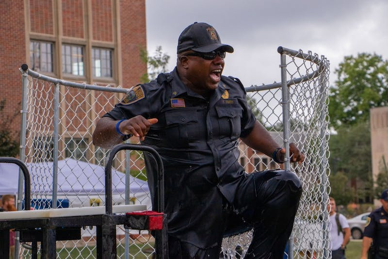 Lieutenant Terrell Smith climbs out of the water tub after being dunked next to the Scramble Light on Aug. 22, 2019. Students could buy two automatic dunks for $10. Jacob Musselman, DN