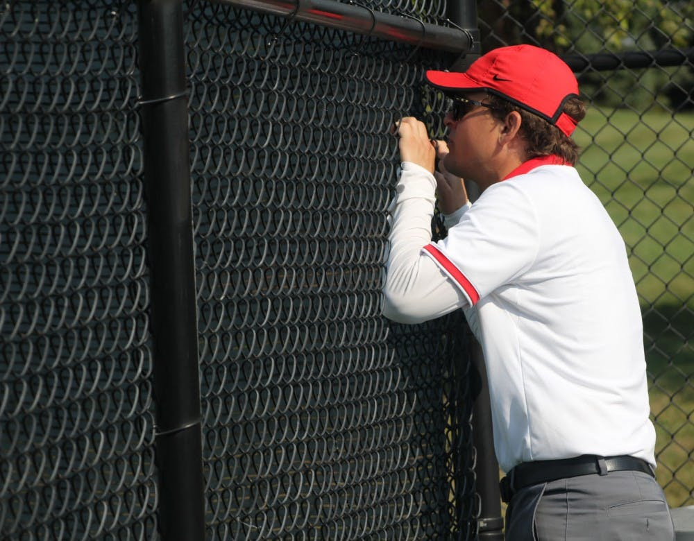 Women's tennis head coach Max Norris talks to senior Sarah Swiderski in her first round singles match against Detroit Mercy. Norris enters his sixth season as head coach of Ball State. Photo by Patrick Murphy