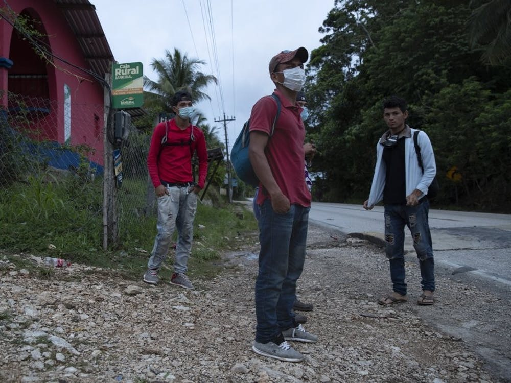 Honduras migrant Olvin Suazo, center, accompanied by others hitch a ride in San Luis Peten, Guatemala, Saturday, Oct. 3, 2020. Early Saturday, hundreds of migrants who had entered Guatemala this week without registering were being bused back to their country's border by authorities after running into a large roadblock. (AP Photo/Moises Castillo)