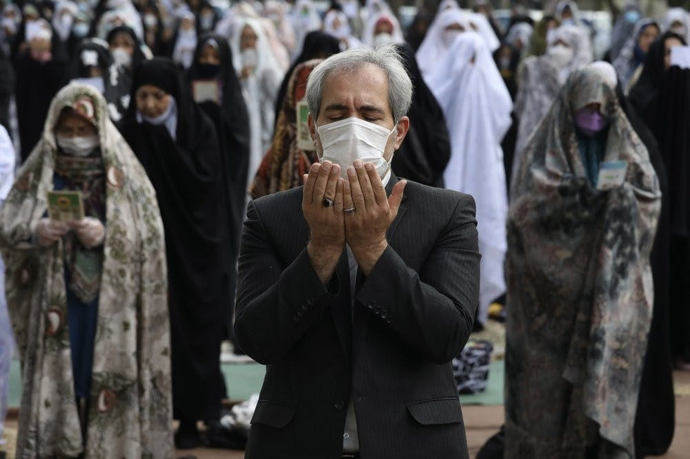 <p>Worshippers wearing protective face masks offer Eid al-Fitr prayers outside a mosque May 24, 2020, in Tehran, Iran. Muslims worldwide celebrate one of their biggest holidays under the long shadow of the coronavirus. <strong>(AP Photo/Vahid Salemi)</strong></p>