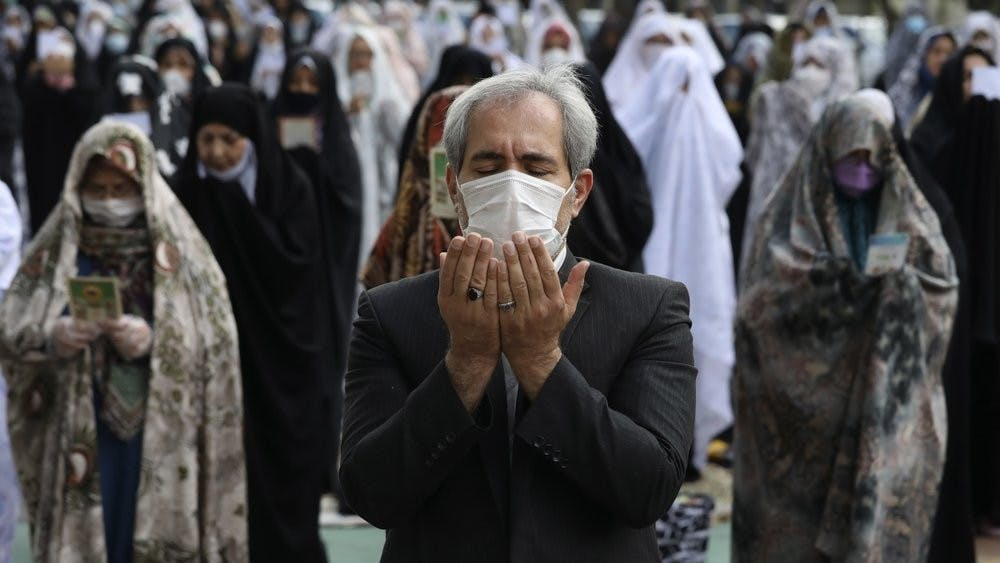 Worshippers wearing protective face masks offer Eid al-Fitr prayers outside a mosque May 24, 2020, in Tehran, Iran. Muslims worldwide celebrate one of their biggest holidays under the long shadow of the coronavirus. (AP Photo/Vahid Salemi)