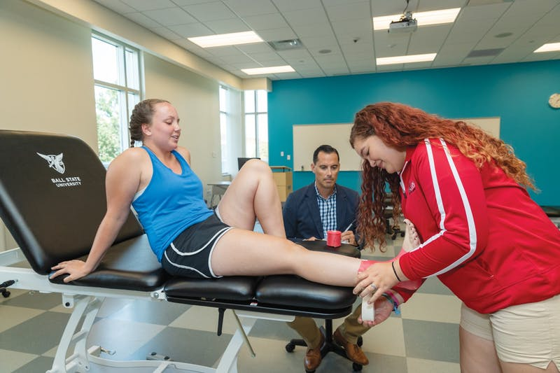 Zach Dougal, assistant clinical professor of athletic training, works with his athletic training students to wrap a person's foot on a treatment table. Ball State University, Photo Provided