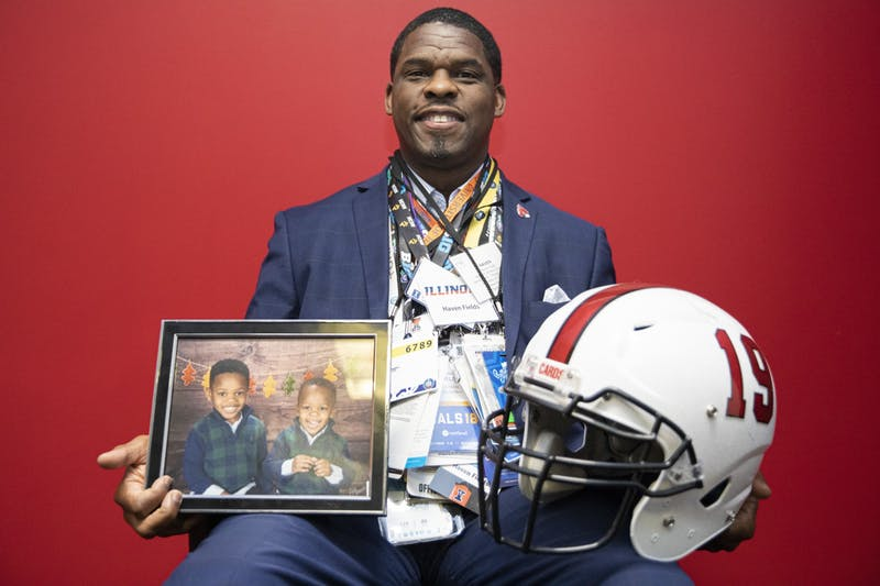 Haven Fields, deputy athletic director poses for a portrait wearing all of his press passes and holding a Ball State football helmet and a portrait of his two sons, April 19, 2021, in his office in the Health and Physical Activity building. Jacob Musselman, DN