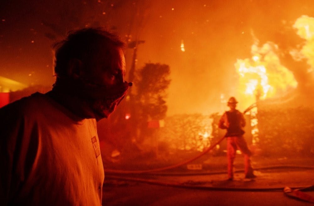 <p>A man walks past a burning home during the Getty fire, Oct. 28, 2019, in Los Angeles, Calif. <strong>(AP Photo/ Christian Monterrosa)</strong></p>