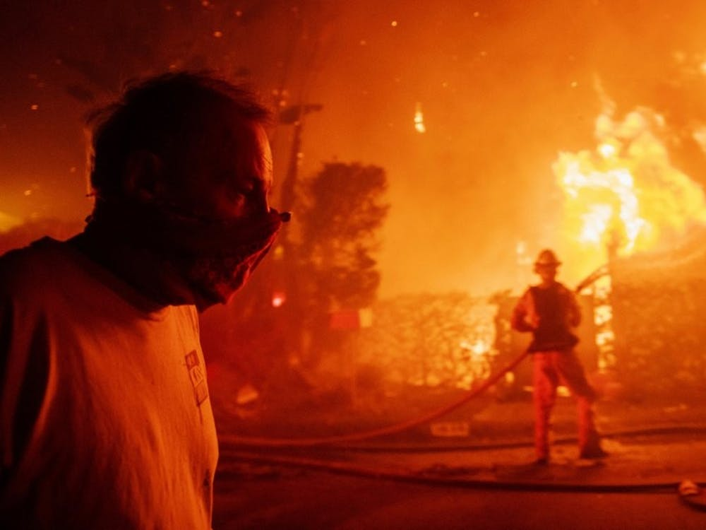 A man walks past a burning home during the Getty fire, Oct. 28, 2019, in Los Angeles, Calif. (AP Photo/ Christian Monterrosa)
