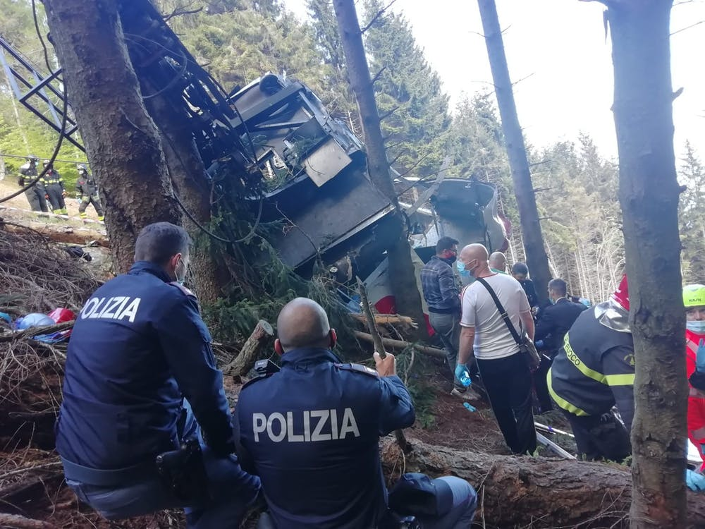 <p>In this handout photo provided by the Italian state police, emergency workers surround the wreckage of a cable car that fell from the Stresa-Alpine-Mottarone line on May 23, 2021 in Stresa, Italy. After initial confusion over the number of passengers, Italian news outlets reported that 15 people had been riding in the cable car before it fell, and officials said two children were taken from the accident site to a hospital in Turin. <strong>(Handout photo by the Italian State Police via Getty Images/TNS)</strong></p>