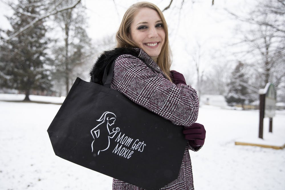 <p>Brittany Scott poses for a portrait with her Mom Gets Moxie tote bag Jan. 16, 2021, at Guthrie Park. On her Mom Gets Moxie Instagram page, Scott posts free workouts for pregnant and postpartum people to do from the comfort of their homes with the equipment they have, such as dumbbells, yoga mats, resistance bands and towels. Jacob Musselman, DN</p>