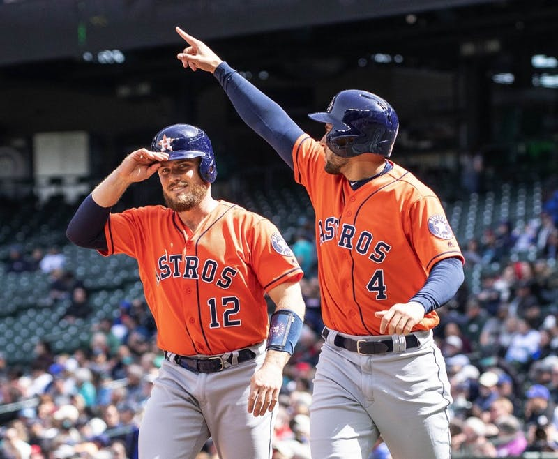 The Houston Astros' George Springer (4) salutes Jose Altuve after he scored on Altuve's bases-loaded double in the fifth inning against the Seattle Mariners Thursday, April 19, 2018, at Safeco Field in Seattle. The Astros won, 9-2. (Dean Rutz/Seattle Times/TNS)
