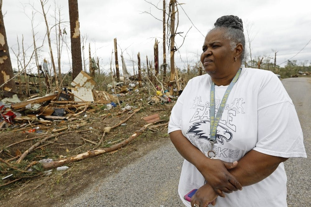 Sarah Cook looks at the remnants of houses and mobile homes April 13, 2020, in this Bassfield, Miss., neighborhood. Harper Town was one of many neighborhoods in Mississippi swept by a series of tornadoes, Sunday afternoon and evening. (AP Photo/Rogelio V. Solis)