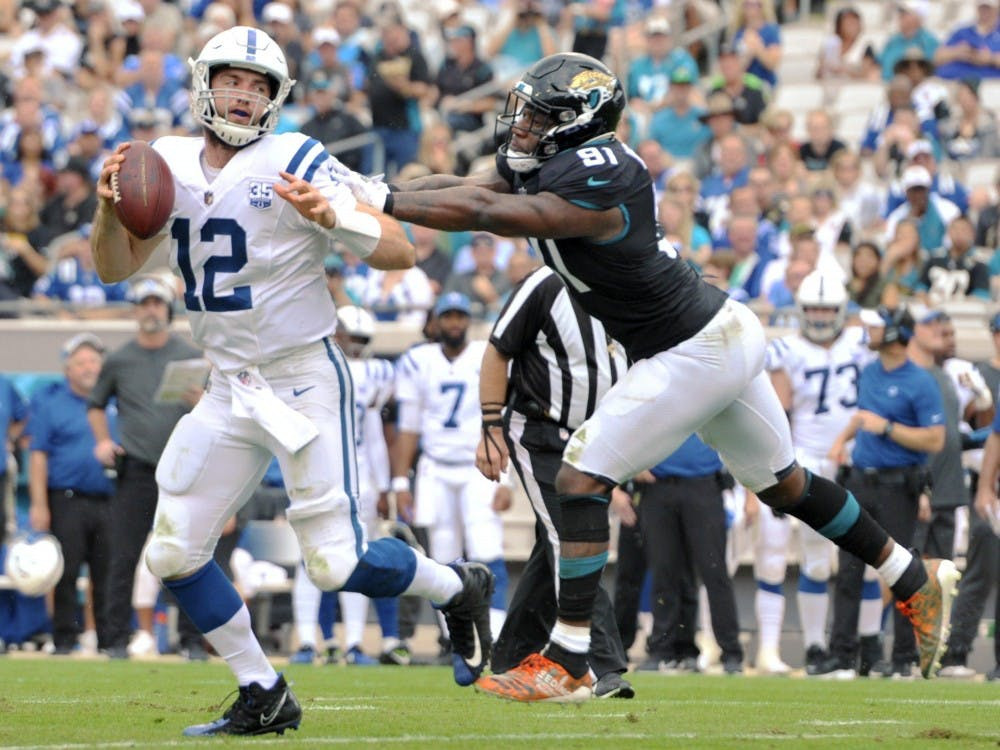 Indianapolis Colts quarterback Andrew Luck (12) tries to elude Jacksonville Jaguars defensive end Yannick Ngakoue (91) on a scramble during early second quarter action. The Jacksonville Jaguars hosted the Indianapolis Colts at TIAA Bank Field in Jacksonville, Florida Sunday, December 2, 2018. The Jaguars went into the half with a 3 to 0 lead. Bob Self/ TNS
