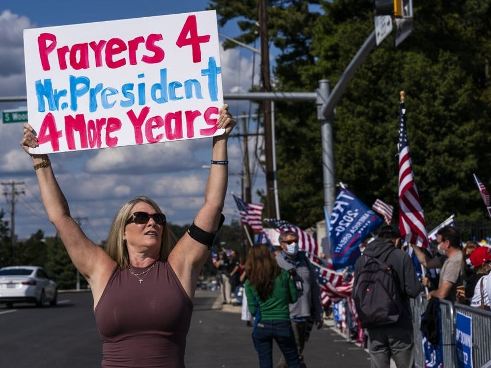 Karen Simon from the District of Columbia, left, waves a banner together with other supporters of President Donald Trump, gathered outside the Walter Reed National Military Medical Center in Bethesda, Md., Monday, Oct. 5, 2020. Trump said Monday he's leaving the military hospital where he has been treated for COVID-19 and will continue his recovery at the White House. (AP Photo/Manuel Balce Ceneta)