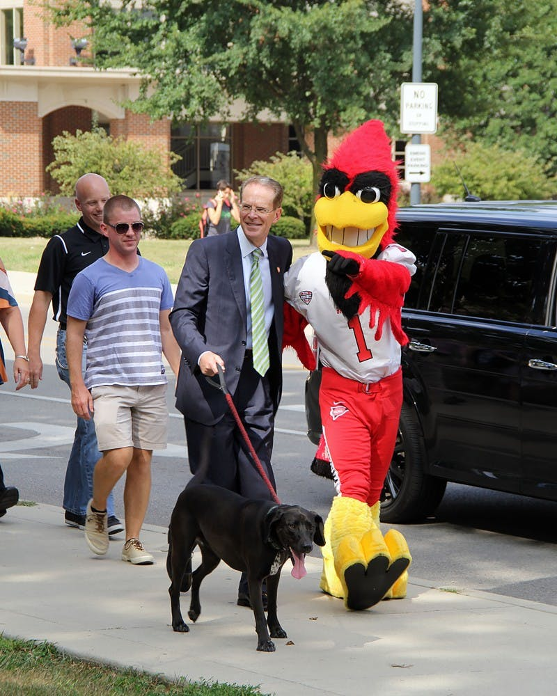 """President Mearns and Charlie Cardinal pose for a photo while walking down N. McKinley Ave. on Wednesday, Aug. 30, 2017 for the kickoff of the On the Road with the Cardinals fitness program. Faculty and staff enrolled in the program have 68 days to """"walk"""" the distance to Cardinals' away football games during the 2017 season. Paige Grider, DN"""